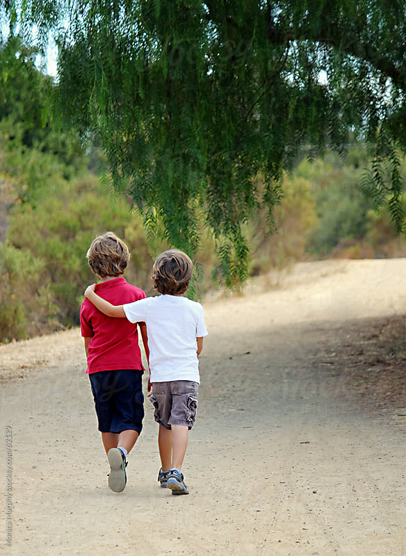 Two boys walking down trail, one with arm around the other, leading into the trees by Monica Murphy for Stocksy United