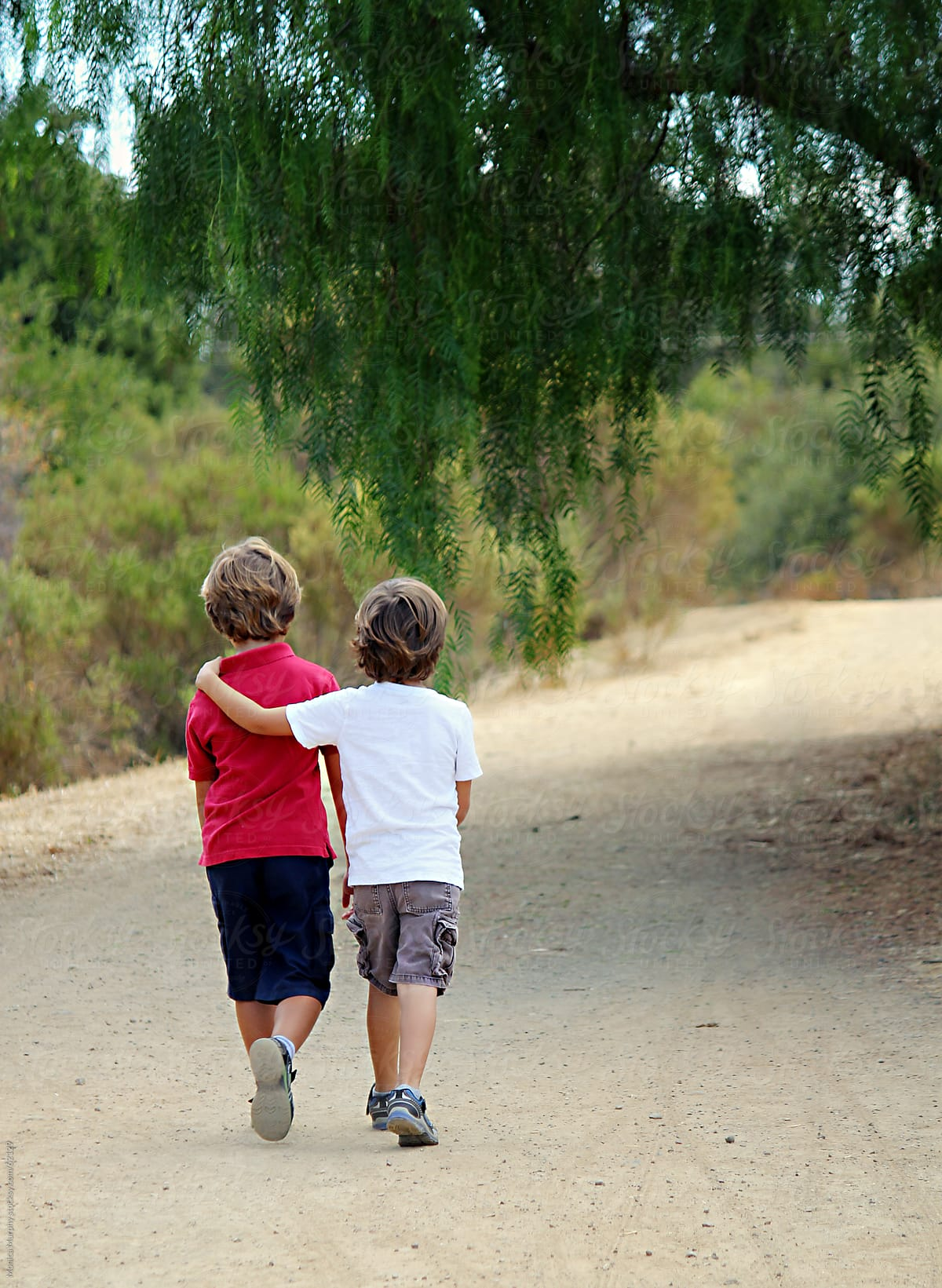 Two Boys Walking Down Trail, One With Arm Around The Other ...
