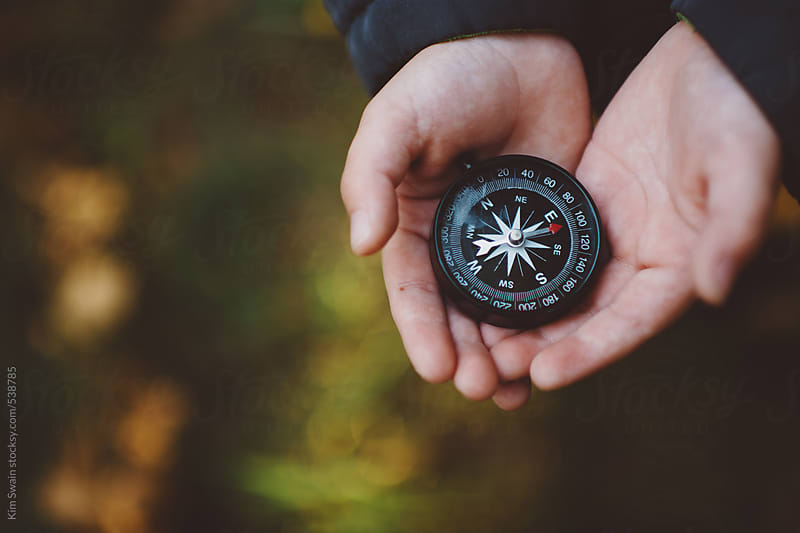 Child't hands with compass by Kim Swain for Stocksy United