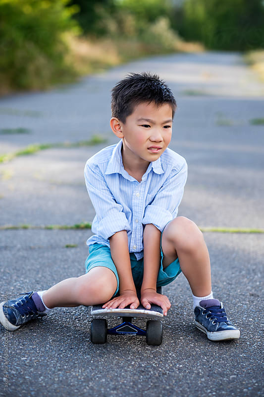Asian kid sitting on his skateboard outdoor in a park by Suprijono Suharjoto for Stocksy United