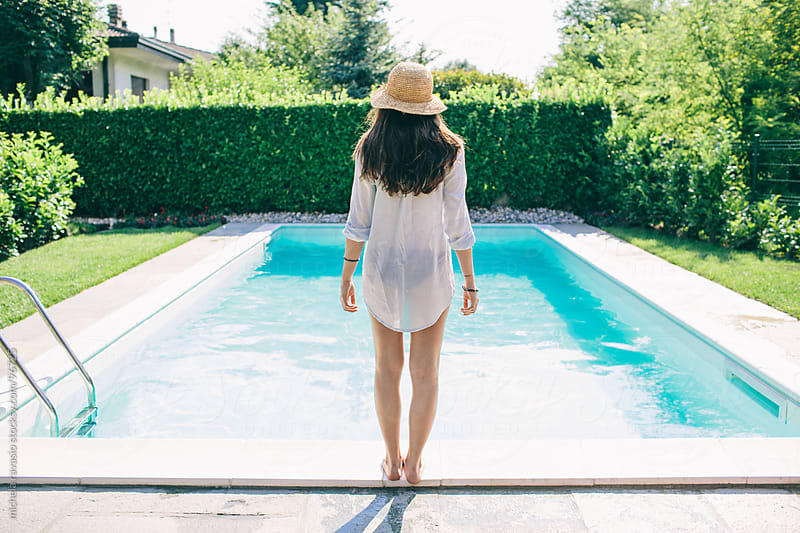 Young woman in swimming pool by michela ravasio for Stocksy United