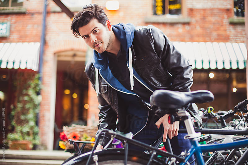 Handsome man locks up his bike. by Cherish Bryck for Stocksy United