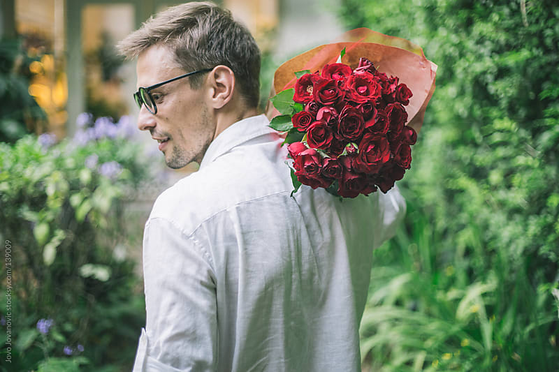Man carrying a bouquet of red roses on his shoulder.  by Jovo Jovanovic for Stocksy United