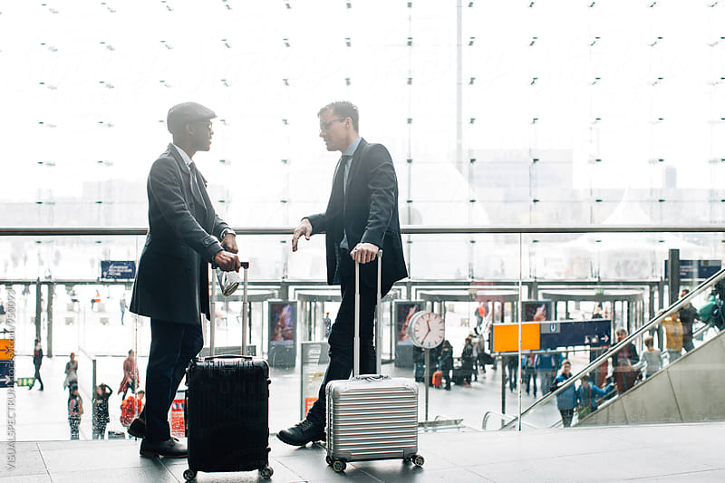 Two Business Travelers Chatting and Waiting in Bright Modern Glass Structure by Julien L. Balmer for Stocksy United