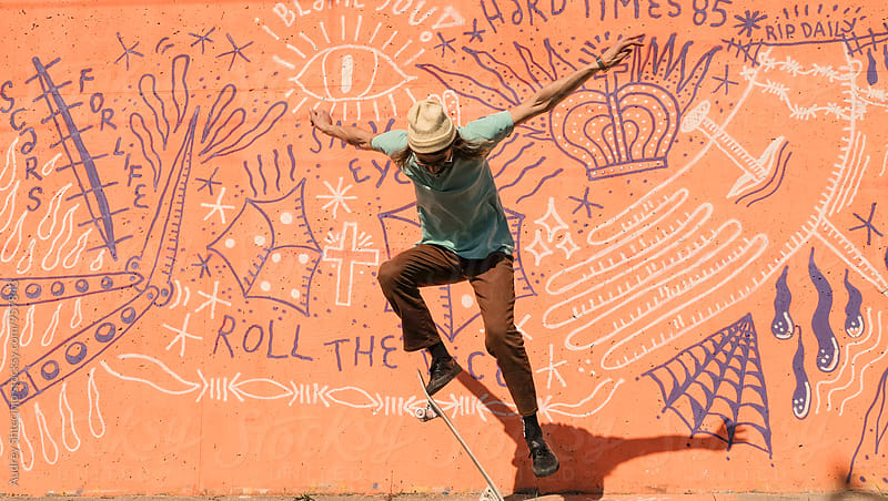 Hip young male in urban outfit doing tricks on skateboard in front of graffiti. by Audrey Shtecinjo for Stocksy United