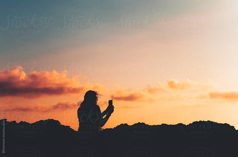 Anonymous, unrecognizable silhouetted female taking a photo of a beautiful sunset with smartphone by Wizemark for Stocksy United