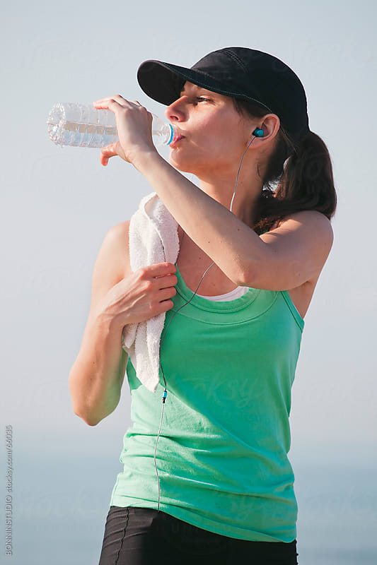 Sport girl listening music and drinking water after a run workout on the beach. by BONNINSTUDIO for Stocksy United