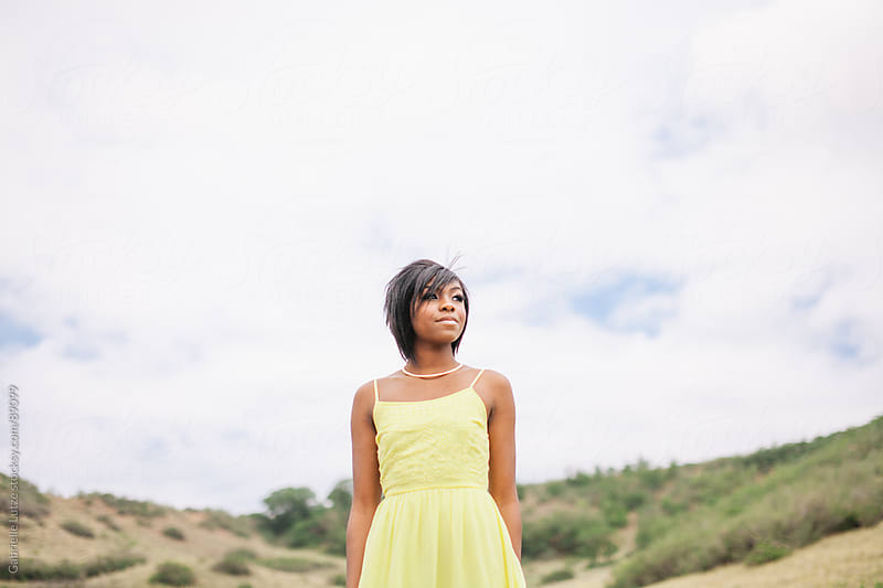 Black girl outside in yellow dress by Gabrielle Lutze for Stocksy United