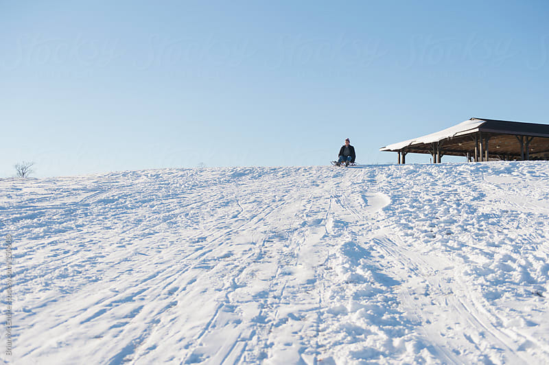 Man with runner sled in distance at sledding hill top by Brian McEntire for Stocksy United