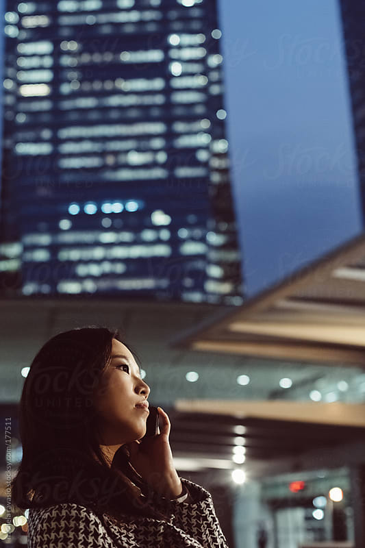 Young asian woman using her cell phone  by michela ravasio for Stocksy United