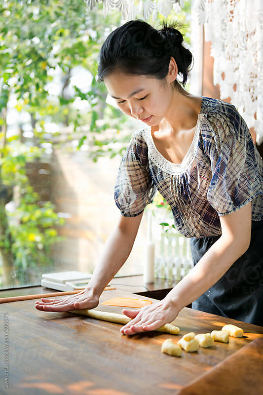 Young woman hands rolling dough for bread by Lawren Lu for Stocksy United