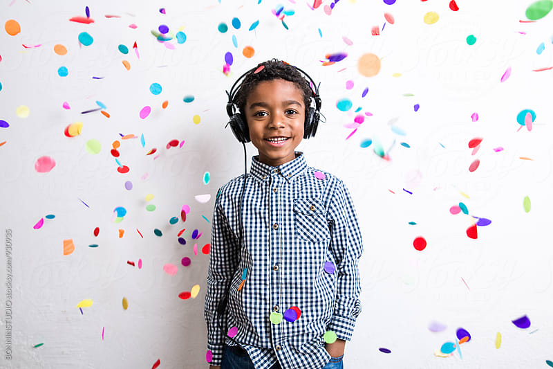 Portrait of a little boy listening music whilst confetti falls from above. by BONNINSTUDIO for Stocksy United