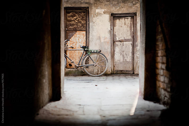 Bicycle in an alley by Christine Love Hewitt for Stocksy United