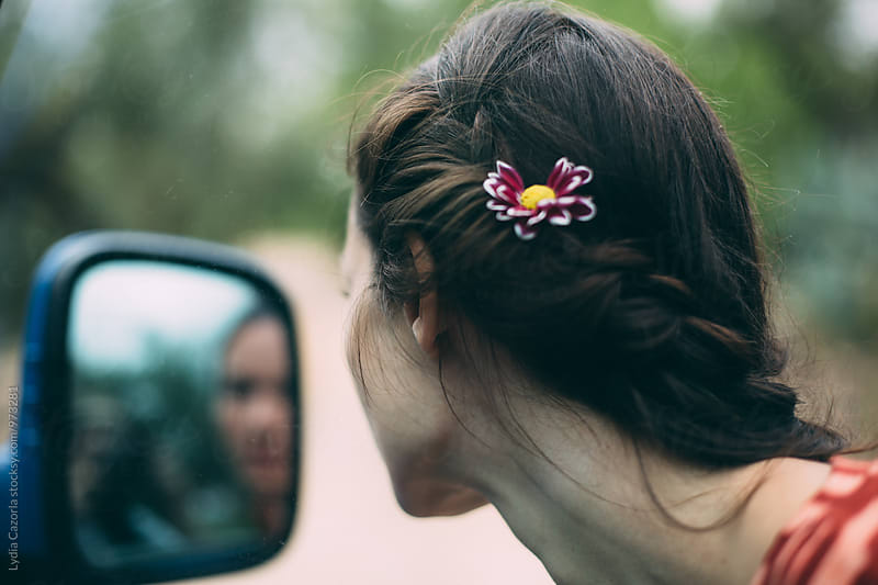 Young woman looking her hair with a flower in the rearview mirror by Lydia Cazorla for Stocksy United