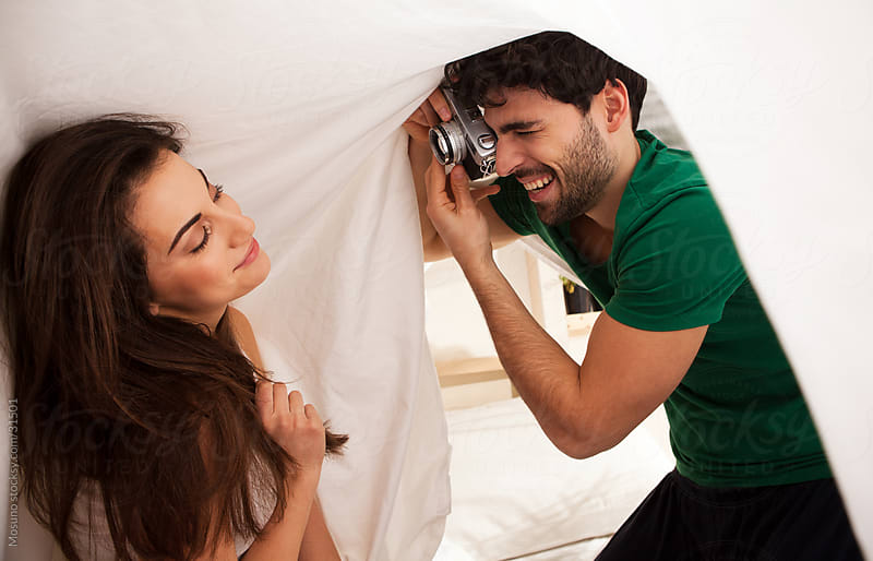 Young carefree couple laughing and taking pictures under the sheets.  by Mosuno for Stocksy United