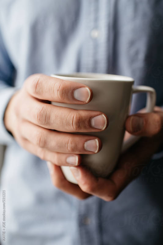 A man holding a mug of coffee by KATIE + JOE for Stocksy United