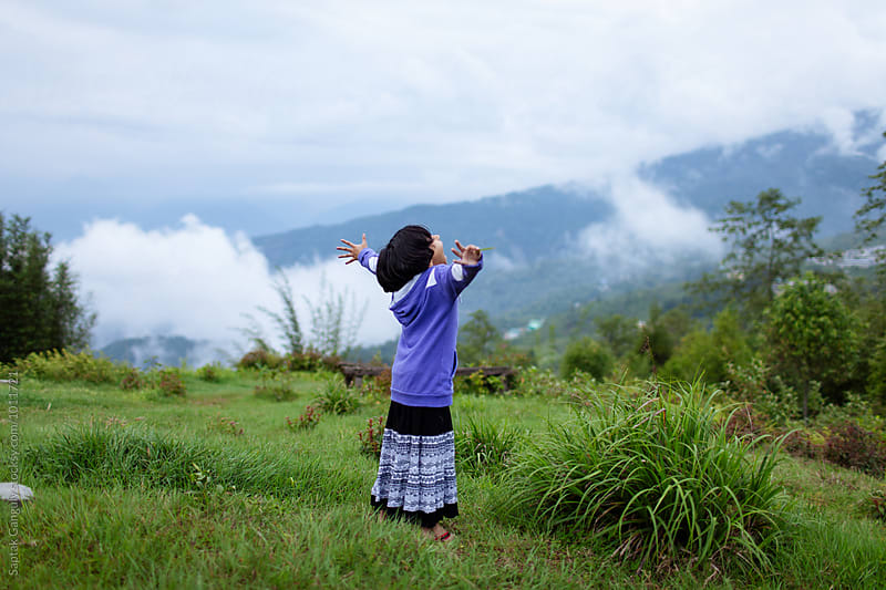 Little girl having fun in the hills on a cloudy day by Saptak Ganguly for Stocksy United