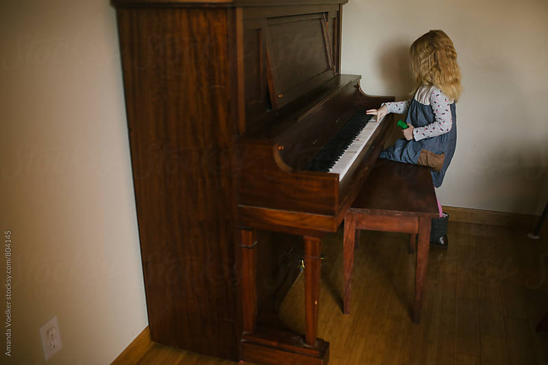 Little Girl Sits at an Antique Piano by Amanda Voelker for Stocksy United