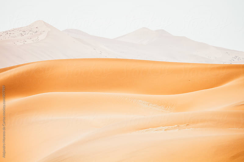 Remote view of sand dunes and mountainous scenery in the background in the desert by Alejandro Moreno de Carlos for Stocksy United