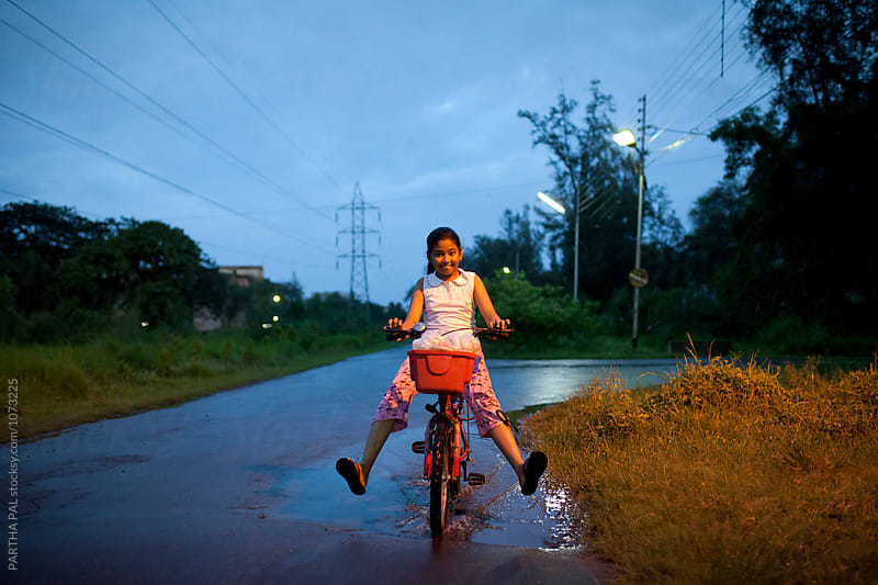 Teenage girl plying and making fun with cycle in blue hour by PARTHA PAL for Stocksy United