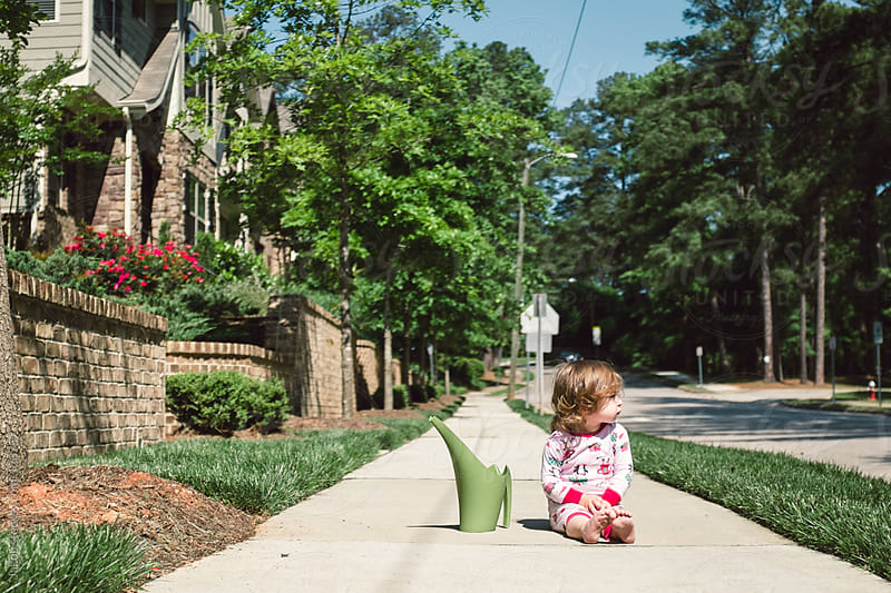 A toddler sitting on a sidewalk, taking a break from watering plants by Jakob for Stocksy United