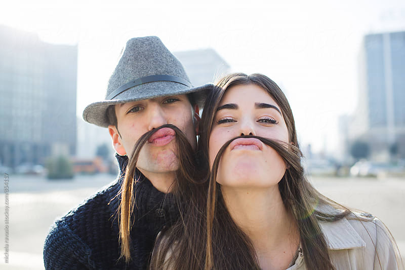 Portrait of playful couple looking at camera by michela ravasio for Stocksy United