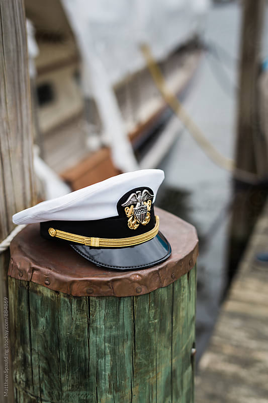 Military naval officer's lid on pier piling - vertical by Matthew Spaulding for Stocksy United