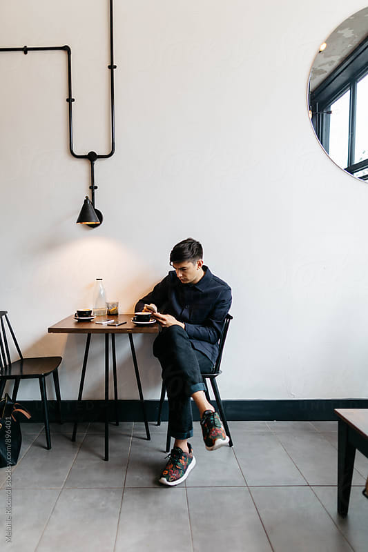 Man texting in coffee shop by Melanie Riccardi for Stocksy United