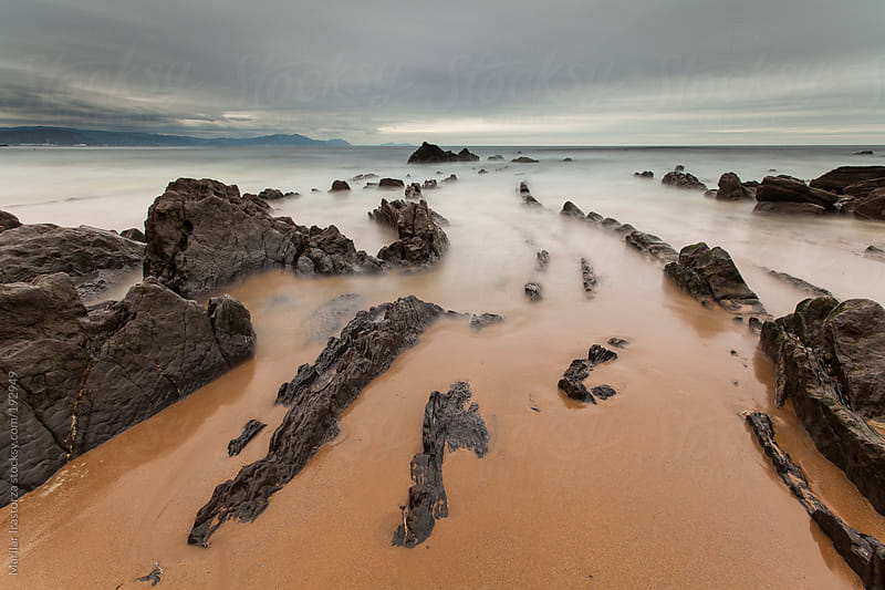 Rocky beach in a cloudy day by Marilar Irastorza for Stocksy United
