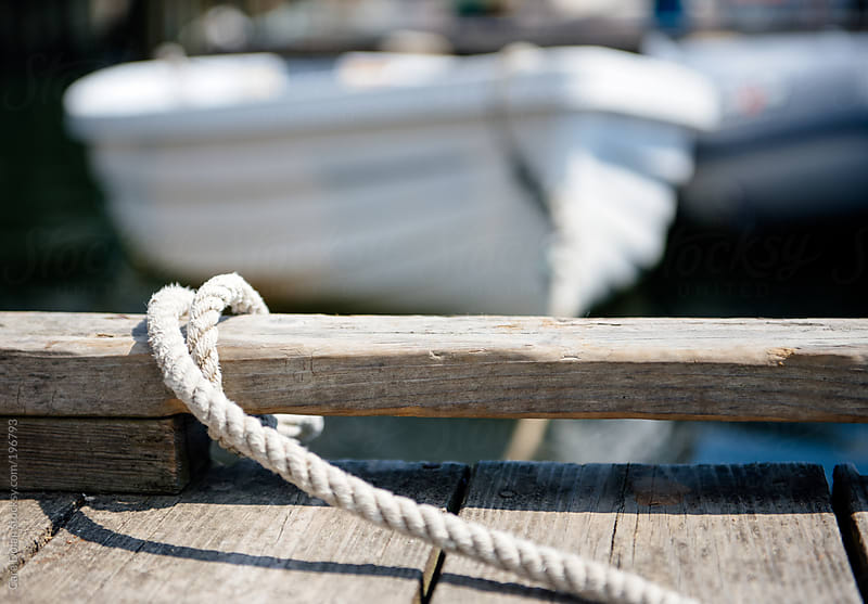 Rowboat is tied to a dock with rope by Cara Dolan for Stocksy United