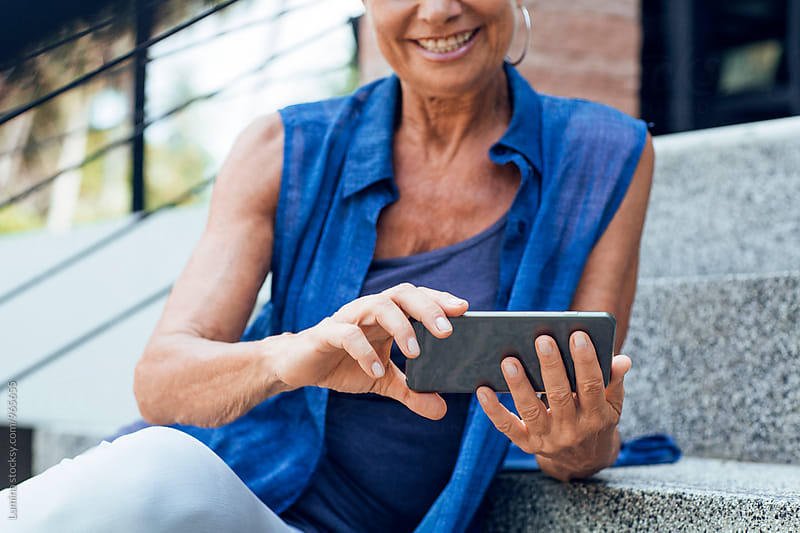 Senior Woman Using a Mobile Phone Outdoors by Lumina for Stocksy United