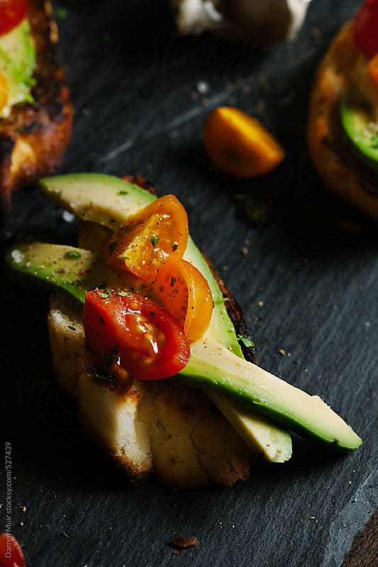 Slice of crostini with avocado and tomato. by Darren Muir for Stocksy United