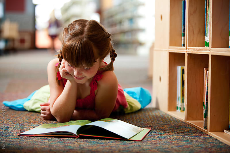Library: Girl Lying Down, Reading a Book by Sean Locke for Stocksy United