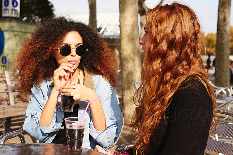 two women drinking oda at the urban park by Guille Faingold for Stocksy United