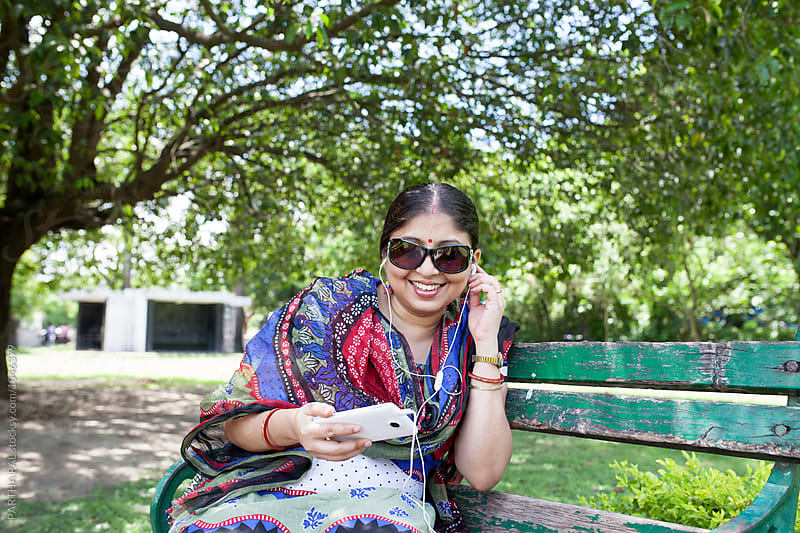 Beautiful woman using smartphone happily by PARTHA PAL for Stocksy United