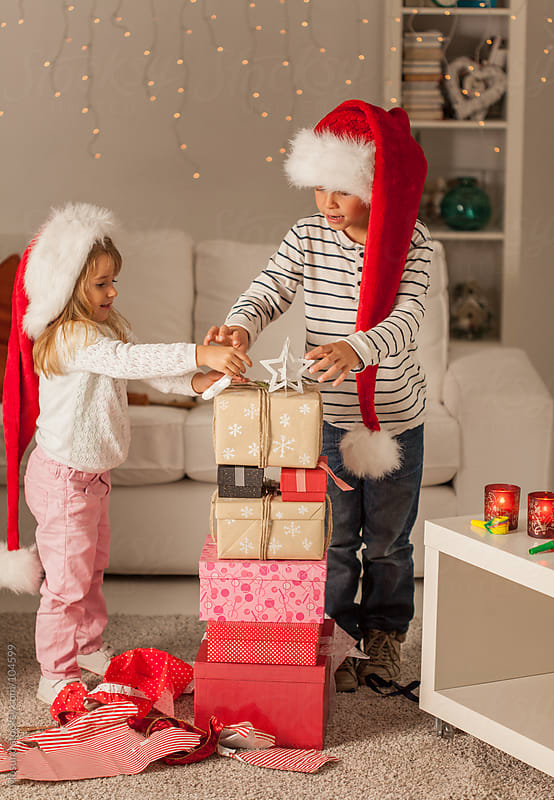 Children Arranging Christmas Gifts by Mosuno for Stocksy United
