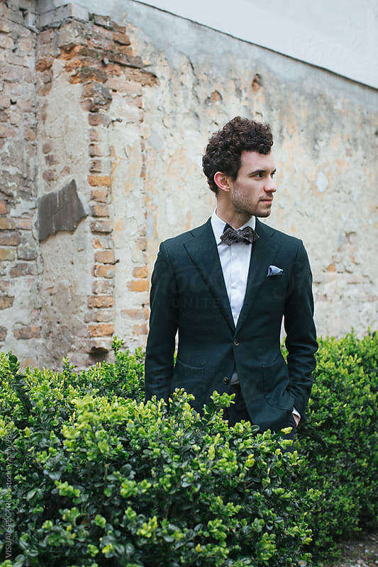 Outdoor Portrait of Handsome Stylish Caucasian Man in Green Jacket and Bow Tie by Julien L. Balmer for Stocksy United