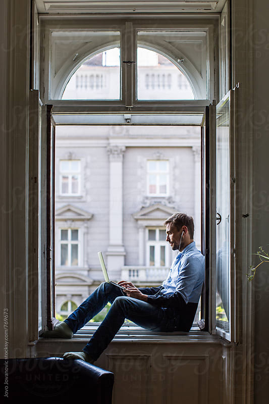 Man sitting at the window and working on a computer by Jovo Jovanovic for Stocksy United