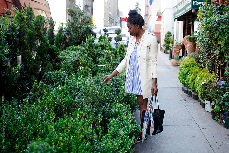 Woman on city street looking at bushes by Jennifer Brister for Stocksy United