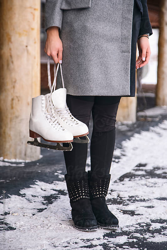 Young woman holding white skates by Danil Nevsky for Stocksy United