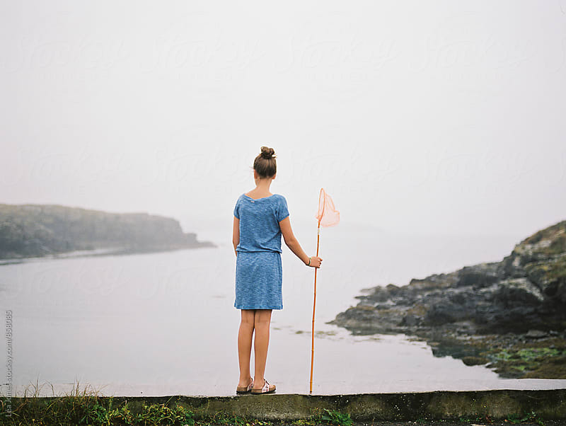 girl standing by a cove with fishing net by Léa Jones for Stocksy United