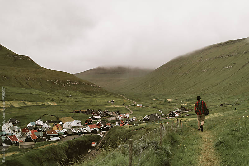Boy Walking along Mountains in Gjogv, Faroe Islands by Rachel Gulotta Photography for Stocksy United