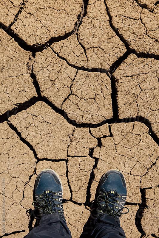 Feet on a dry cracked surface. by Shikhar Bhattarai for Stocksy United
