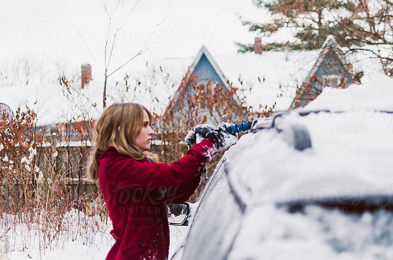 girl removes snow from a car by Deirdre Malfatto for Stocksy United
