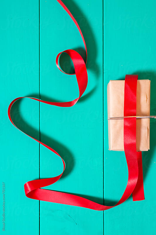 Christmas present with red ribbon by Bisual Studio for Stocksy United