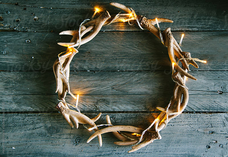 An antler wreath with fairy lights. by Helen Rushbrook for Stocksy United