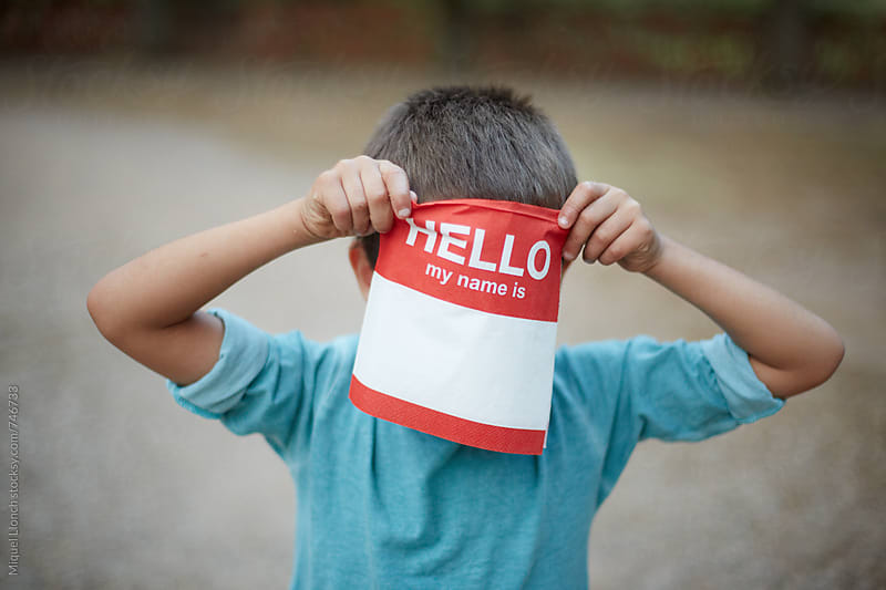 Young boy hiding his face behind a paper napkin with the word hello by Miquel Llonch for Stocksy United