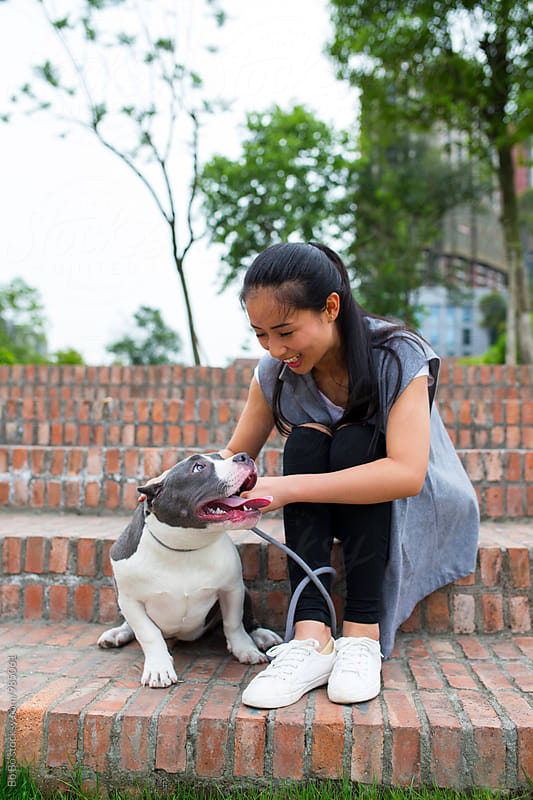 one young asian woman with her dog in the park by Bo Bo for Stocksy United
