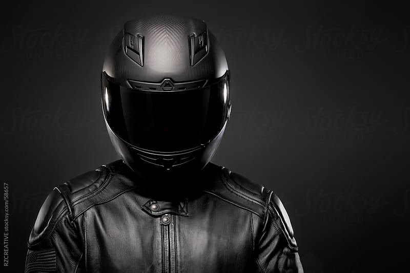 Man wearing a black leather motorcycle jacket and helmet on dark background. by RZ CREATIVE for Stocksy United