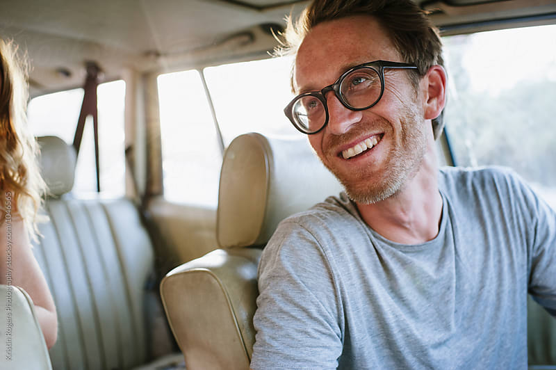 Man with glasses smiling while sitting in car by Kristin Rogers Photography for Stocksy United